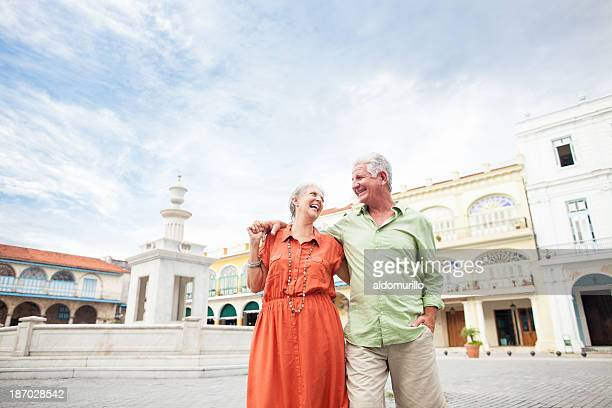 Senior couple laughing and walking by the town square