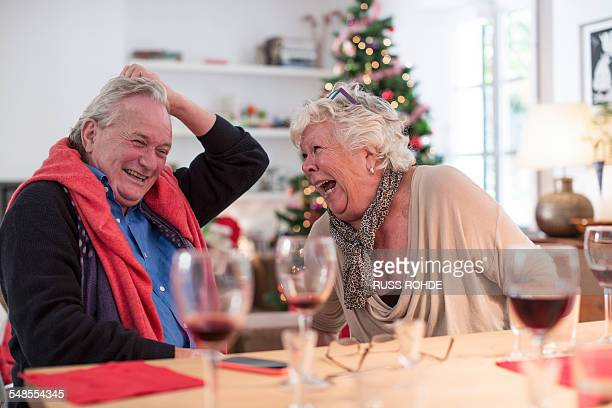Senior couple laughing at christmas lunch table