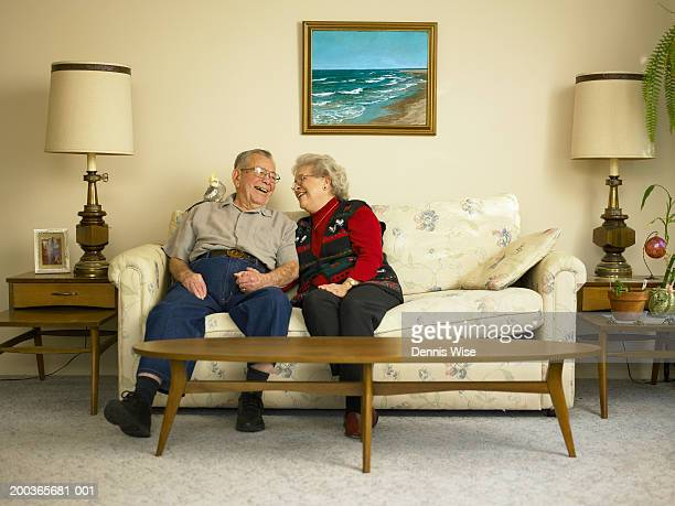 Senior couple laughing on sofa, bird perched on man's shoulder