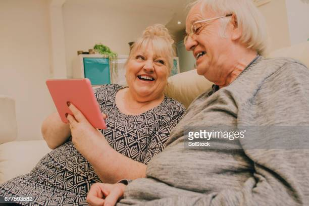 senior couple laughing on the digital tablet! - funny fat women stock pictures, royalty-free photos & images