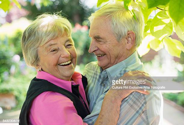 Senior couple laughing whilst waltzing in garden