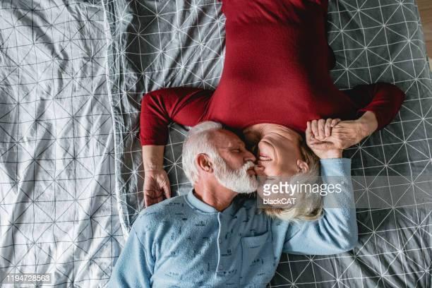 coppia anziana sdraiata a letto - amanti letto foto e immagini stock
