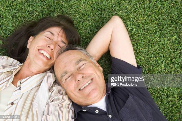 senior couple laying in grass - southern european descent stock pictures, royalty-free photos & images