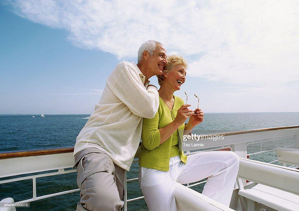 Senior couple leaning on railing, smiling. : Stockfoto