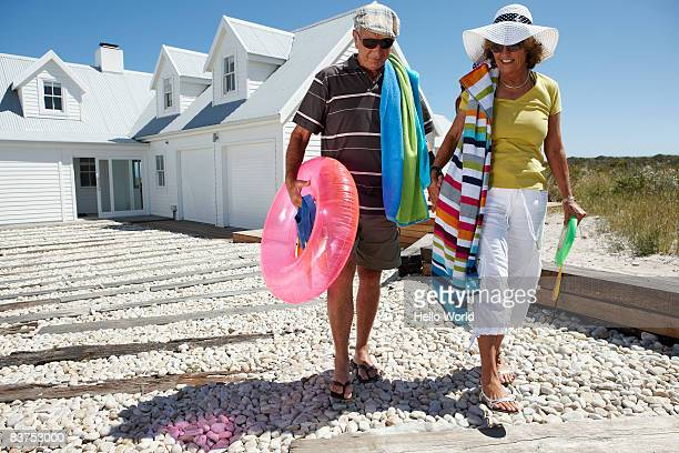 senior couple leaving house with beach toys