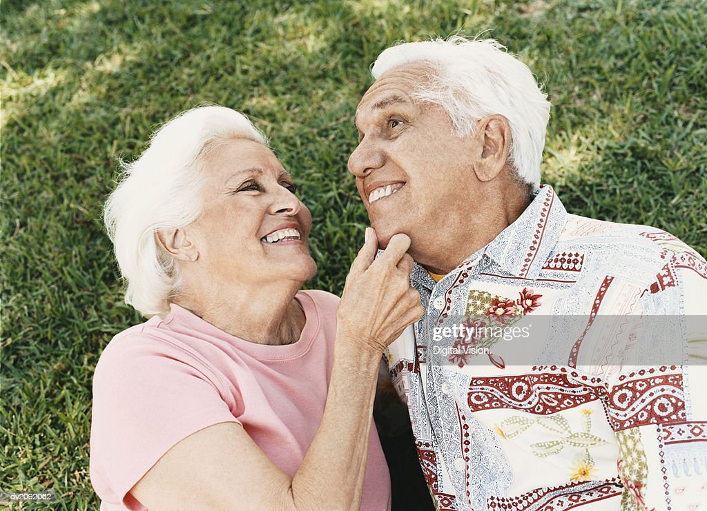 Senior Couple Lie on the Grass, Embracing : Stock Photo