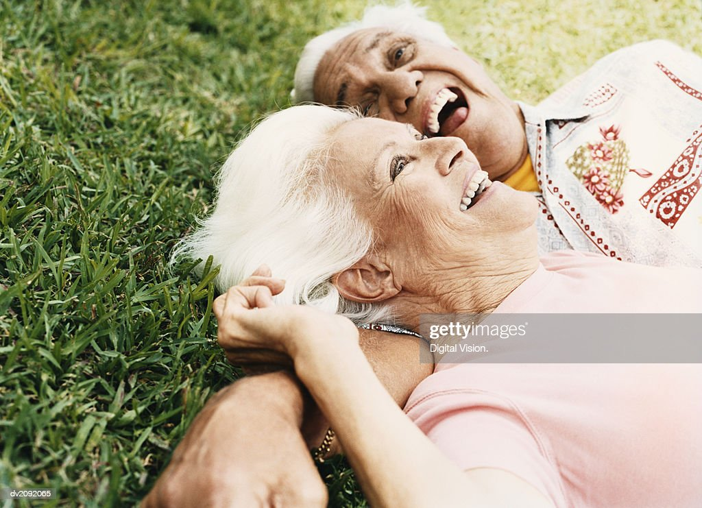 Senior Couple Lie on the Grass, Laughing : Stock Photo