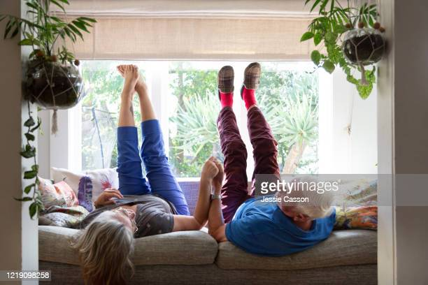 a senior couple lie on the sofa with their legs in the air - retirement stock pictures, royalty-free photos & images