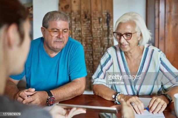 保険代理店セールスピッチを聴くシニアカップル - 加入 ストックフォトと画像