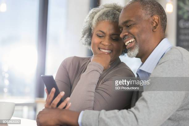 Senior couple look at smart phone together
