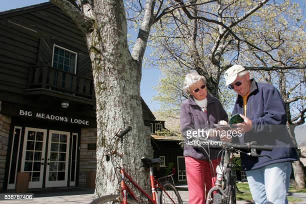 Senior couple looking at a brochure standing next to bicycles at Big Meadows Lodge.