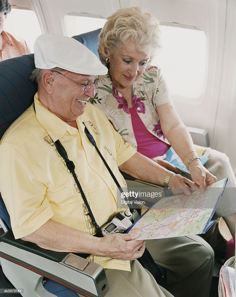 Senior Couple Looking at a Map on a Plane : Stock Photo