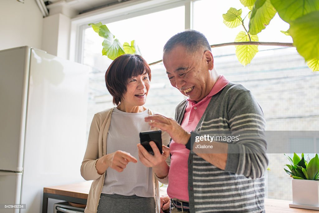 Senior couple looking at a smartphone laughing : Stock Photo