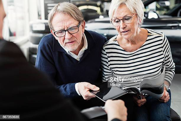 Senior couple looking at agreement in car dealership