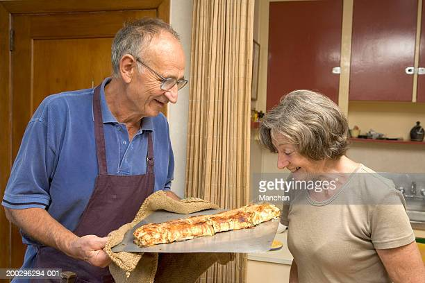 Senior couple looking at apple strudel on baking tray, smiling