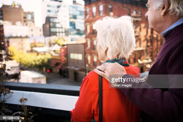 Senior couple looking at city view while standing on balcony