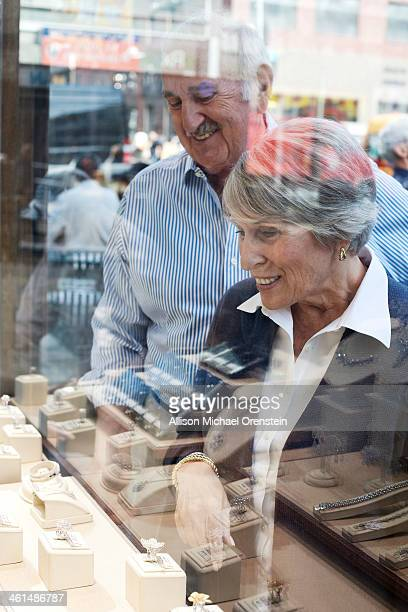 senior couple looking at jewelry in shop window