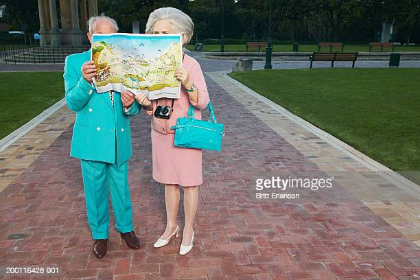 Senior couple looking at map outdoors