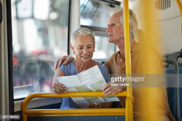 Senior couple looking at map, while riding public bus