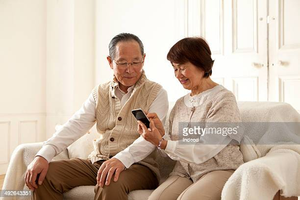 Senior couple looking at mobile phone on sofa