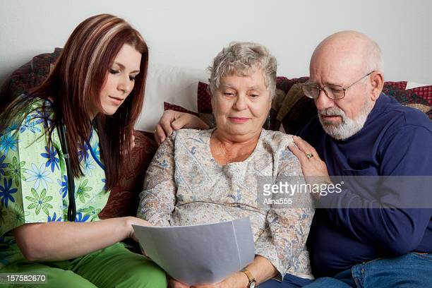 Senior couple looking at papers with young nurse in scrubs