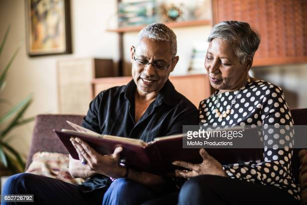 senior couple (60yrs) looking at photo album on couch at home - nostalgia stock pictures, royalty-free photos & images