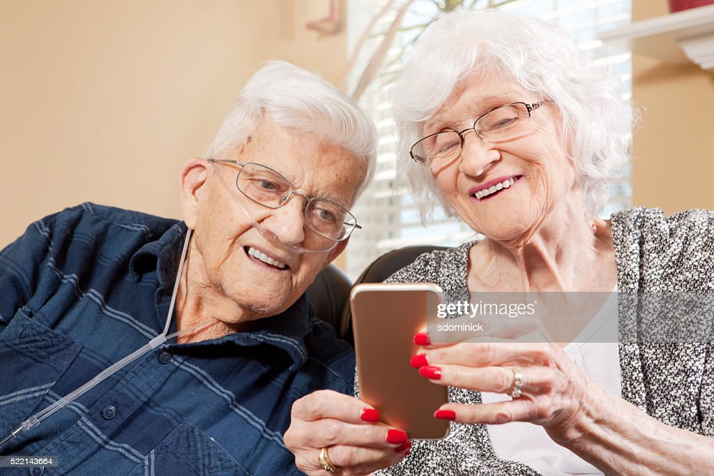 Senior Couple Looking At Smart Phone : Stock Photo