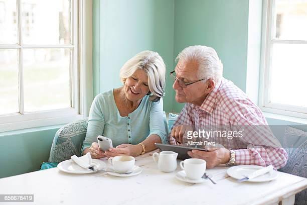 senior couple looking at smart phone - 65 69 jaar stockfoto's en -beelden