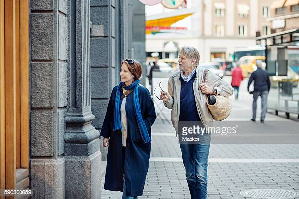 Senior couple looking at store window while walking on city street
