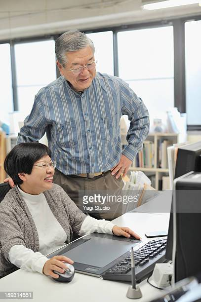 senior couple looking at the computer - working seniors stock pictures, royalty-free photos & images