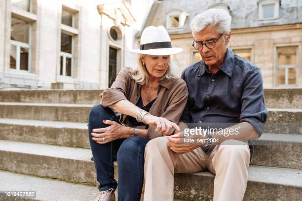 senior couple looking at the map - ile de france stock pictures, royalty-free photos & images