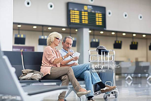 Senior Couple looking at the mobile phone at the airport