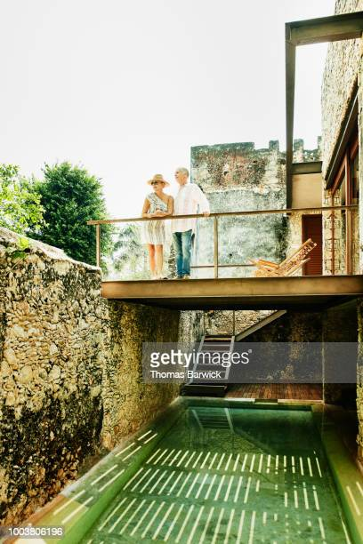 Senior couple looking at view while standing on balcony outside of room at luxury resort