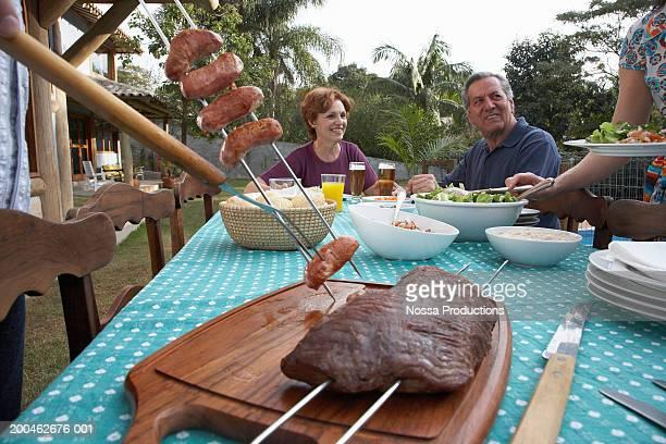 Senior couple looking at woman taking salad at picnic