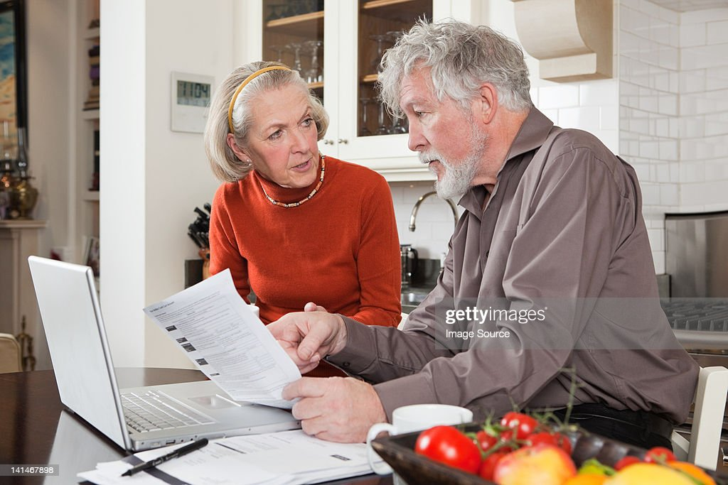 Senior couple looking concerned with bills and laptop : Stock Photo