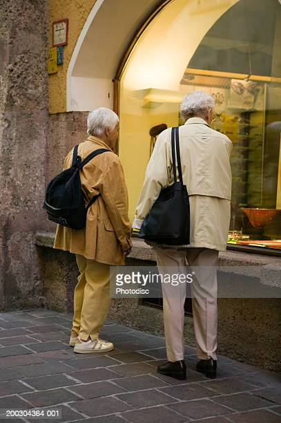 Senior couple looking in shop window on city street