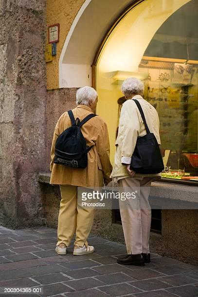Senior couple looking in shop window on city street