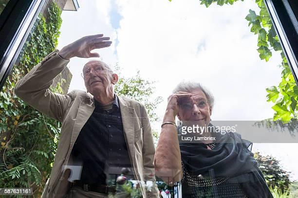 Senior couple looking inside house