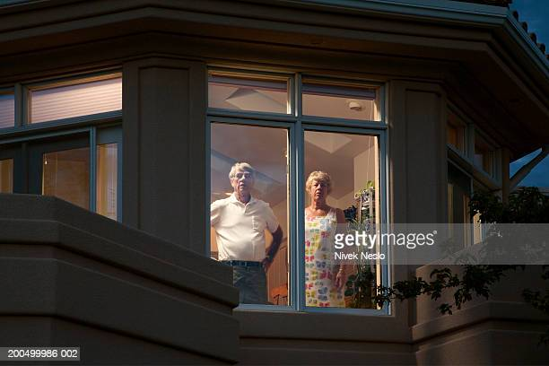 Senior couple looking out of window of suburban house at dusk