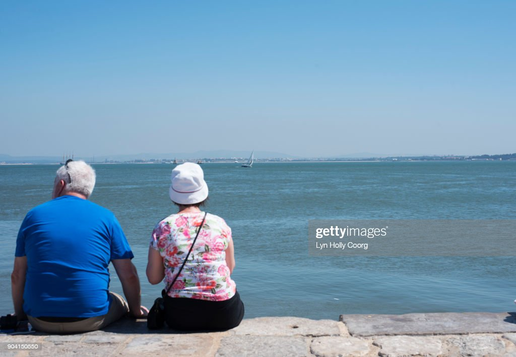 A senior couple looking out over the Tagus River Lisbon . : Stock Photo