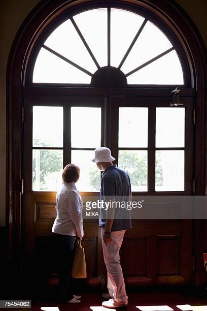 Senior couple looking out window