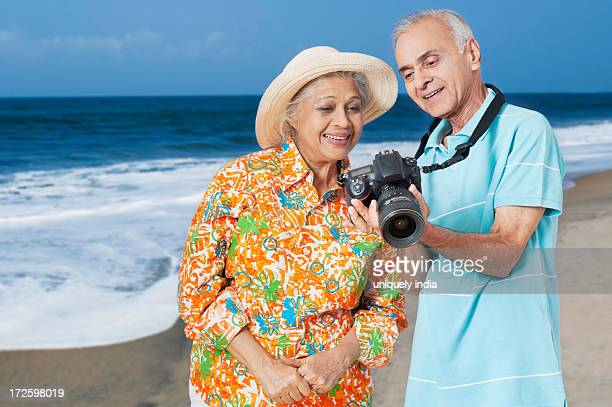 Senior couple looking photographs in a digital camera
