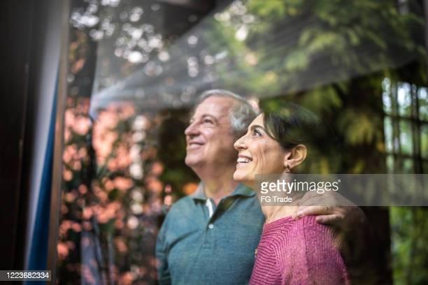 casal de idosos olhando pela janela - abundância - fotografias e filmes do acervo