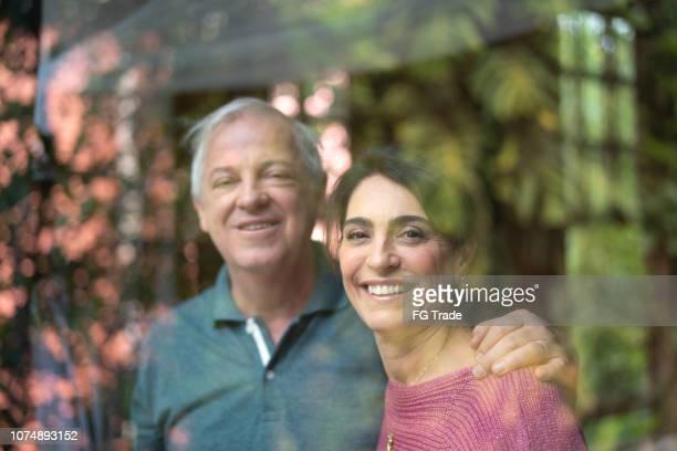 casal sênior olhando através da janela - retrato - 55 59 anos - fotografias e filmes do acervo