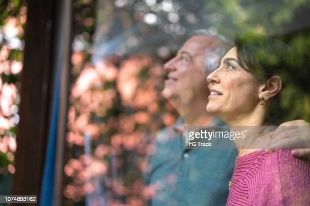 casal sênior olhando através da janela - retrato - processo de envelhecimento - fotografias e filmes do acervo