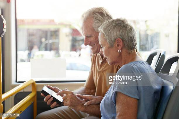 senior couple, looking together at smartphone, while riding public bus - part of a series stock pictures, royalty-free photos & images