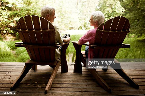 Senior Couple Lounging in Adirondack Chairs on a Wood Deck