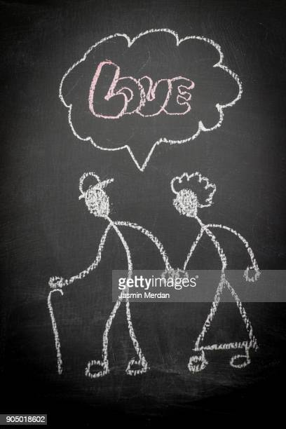 Senior couple love illustrated with chalk on blackboard