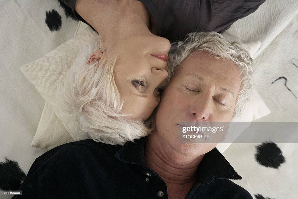 Senior couple lying head to head on a cowskin : Stock Photo