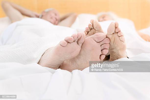 senior couple lying in bed - old lady feet stock pictures, royalty-free photos & images